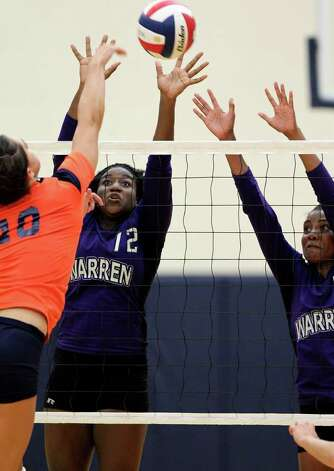 Warren's Laycia Robinson (12) and Jasmine Richardson defend a shot by Brandeis' Andrea Casanova during the Warriors' victory on Tuesday, Aug. 23, 2011 at O'Connor Gym. The victory was Warren's first in district play against the Broncos in seven tries. Photo: Tom Reel/treel@express-news.net / © 2011 San Antonio Express-News
