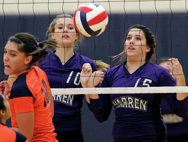 Warren players Shelby Aelvoet (10) and Shaina Garza watch the ball drop for a score behind Brandeis' out-of-position Alex Parker during the Warriors' victory on Tuesday, Aug. 23, 2011 at O'Connor Gym. The victory was Warren's first in district play against the Broncos in seven tries. Photo: Tom Reel/treel@express-news.net / © 2011 San Antonio Express-News
