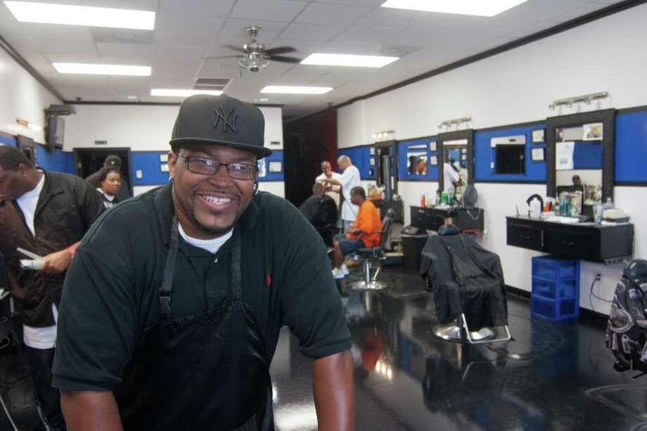 Darrick ?Money? Brown keeps busy at Thirty-II-Degreez Barber Shop, which he owns in west Houston on Fort Bend's west side. Photo: R. Clayton McKee, Freelance / © R. Clayton McKee