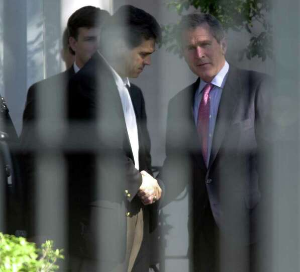 Lt. Governor Rick Perry shakes the hand of George W. Bush at the Governor's Mansion, Nov. 9, 2000 in