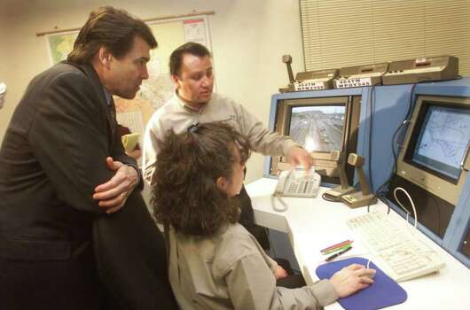 Texas Gov. Rick Perry listens to Ricardo Cortez, back, and Thelma Ramirez describe how traffic is monitored in the traffic management system department at the El Paso Texas Department of Transportation office, March 1, 2001, in El Paso. Photo: LINDA STELTER, AP / EL PASO TIMES