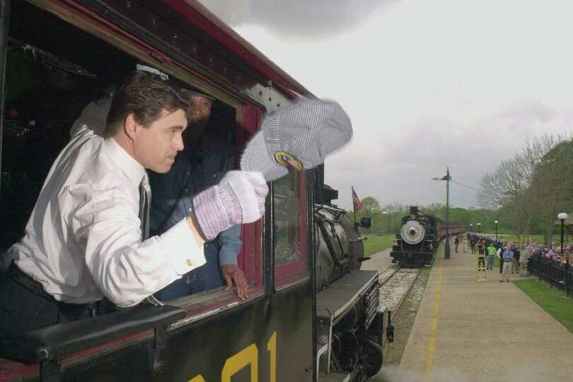 Aboard 100-year-old engine No. 201, Gov. Rick Perry blows the whistle in preparation for the Governo