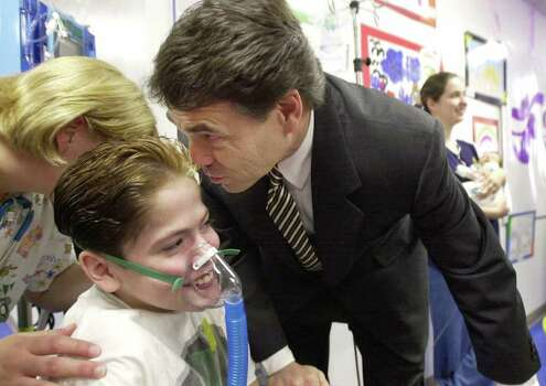 Texas Gov. Rick Perry whispers in the ear of Troy, a patient at Christus Santa Rosa Children's Hospital, in San Antonio, June 19, 2001. Perry stopped at the hospital for a Medicaid simplification ceremonial bill signing. Photo: ERIC GAY, AP / AP