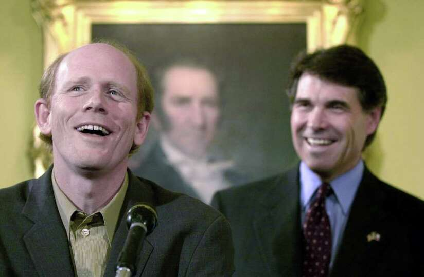 Director Ron Howard laughs with Gov. Rick Perry during a press conference at the Governor's Mansion,