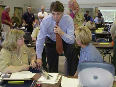 Texas Gov. Rick Perry talks with Linda Stubblefield (left) and Gayle Cross during a terrorism response exercise being conducted in Harris County by the state's Division of Emergency Management, May 22, 2002, in Houston. Photo: PAT SULLIVAN, AP / AP