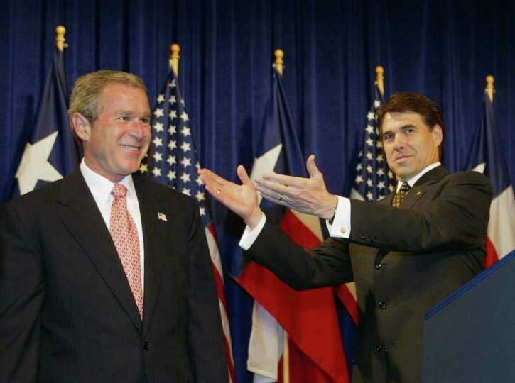President George W. Bush receives a welcome from Texas Governor Rick Perry during 'Texans for Rick P