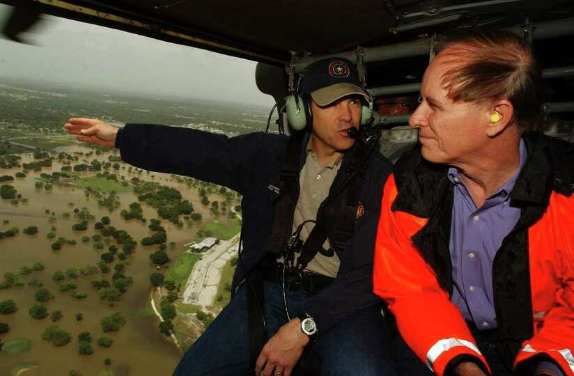 Gov. Rick Perry gestures to Bexar County Judge Nelson Wolff as they fly over flooded areas in a Texa