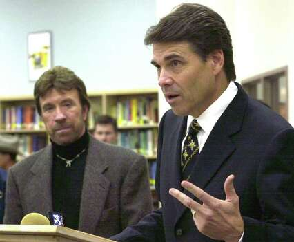 Texas Gov. Rick Perry, right, speaks during a news conference after appearing at an anti-drug assembly,Oct. 11, 2002, with actor Chuck Norris at Lubbock Cooper High School in Lubbock. Photo: JIM WATKINS, AP / LUBBOCK AVALANCHE-JOURNAL