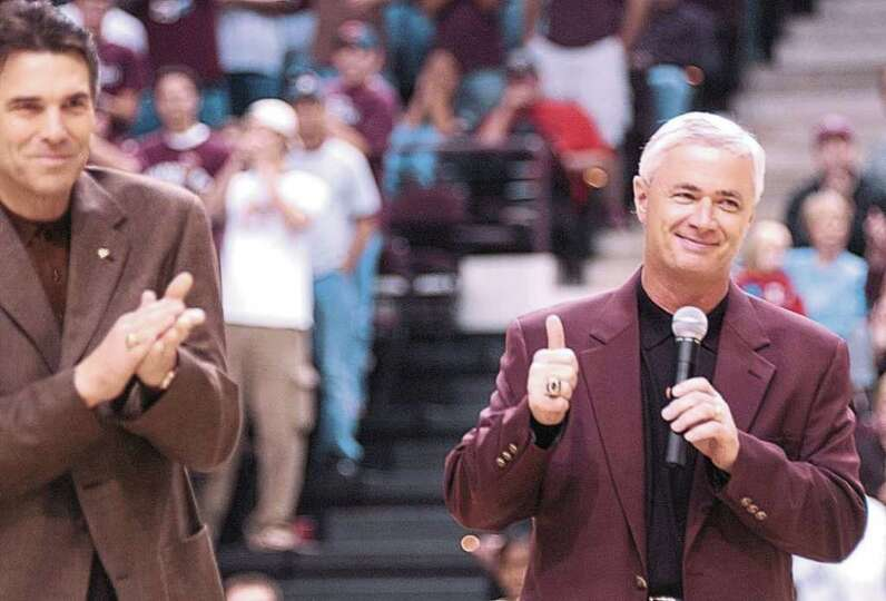 Texas Gov. Rick Perry applauds after introducing new Texas A&M football coach Dennis Franchione to t