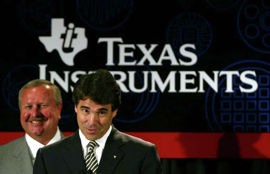 Texas Gov. Rick Perry and president of Texas Instruments Tom Engibous announce a major chip-making expansion at The University of Texas at Dallas in Richardson, June 30, 2003. A new $2 billion semiconductor plant will be developed at the university. Photo: MIKE FUENTES, AP / AP
