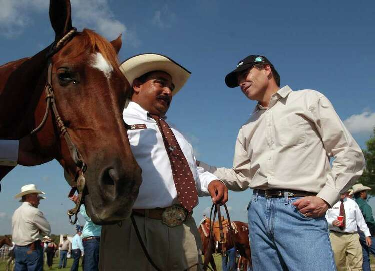 Gov. Rick Perry, right, talks with Candy Aguilar, Oct. 4, 2003, before the start of the King Ranch 1