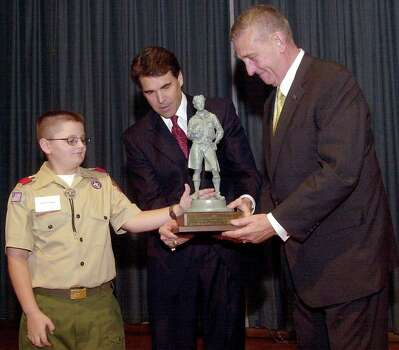 Dalton Ballard (from left) of Greenwood's Scout Troop 158 and Gov. Rick Perry award retired Gen. Tommy Franks with the Distingushed Citizens Award, Oct. 30, 2003 in Midland.  Franks was a member of Scout Troop 158 as a youth growing up in Midland. Photo: KRIS J. MURANTE, AP / MIDLAND REPORTER TELEGRAM