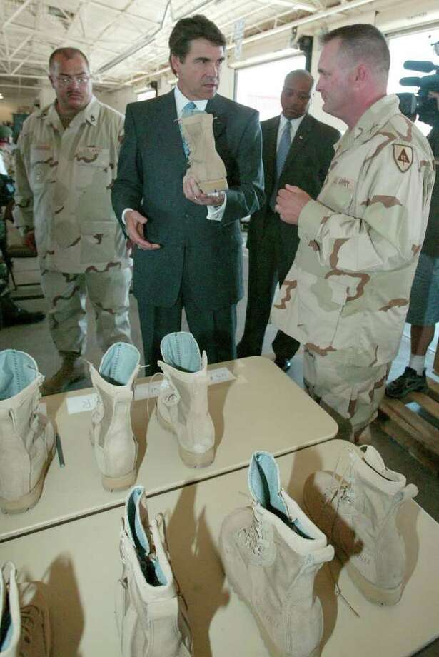 Texas Gov. Rick Perry looks at new combat boots with Maj. Chris Carrier, right, at the deployment facility at Biggs Army Airfield, Aug. 9, 2004, in El Paso. Perry announced a commitment by the state to provide $16.2 million for construction of an overpass-interchange linking Biggs Army Airfield to Fort Bliss. Photo: RUDY GUTIERREZ, *A / EL PASO TIMES