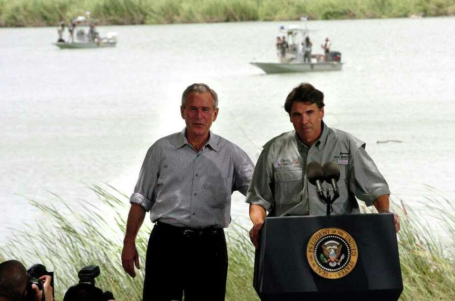 With a background of the Rio Grande River with U.S. Border Patrol and Secret Service patrolling, Gov. Rick Perry and President George W. Bush speak to guests gathered at Anzaldua's Park in Mission, Aug. 3, 2006. Photo: DELCIA LOPEZ, SAN ANTONIO EXPRESS-NEWS / SAN ANTONIO EXPRESS-NEWS