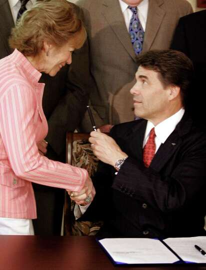 Texas Gov. Rick Perry presents the pen that he used for a ceremonial signing of the school finance b