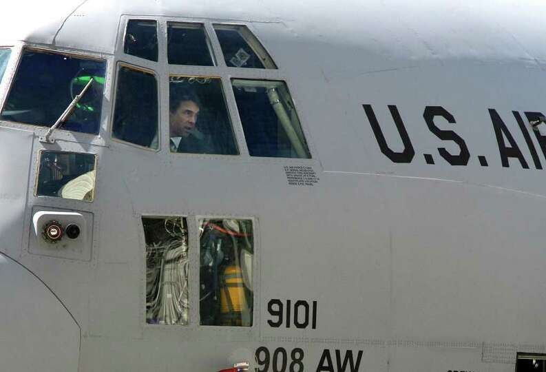 Texas Gov. Rick Perry looks out from the cockpit of a U.S. Air Force C-130 at Boeing in San Antonio.