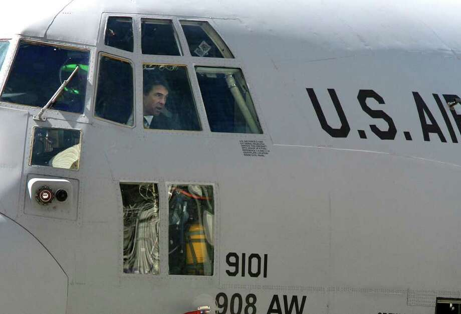 Texas Gov. Rick Perry looks out from the cockpit of a U.S. Air Force C-130 at Boeing in San Antonio.  The plane was recently upgraded through the C-130 Avionics Modernization Program. Photo: ROBERT MCLEROY, SAN ANTONIO EXPRESS-NEWS / San Antonio Express-News