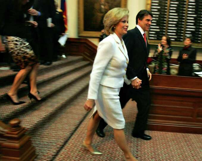 Gov. Rick Perry and his wife Anita leave the floor of the House Chamber after Perry took the oath of