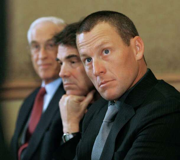 Cycling champion Lance Armstrong (right) a cancer survivor, sits with Dr. John Mendelsohn (left) and