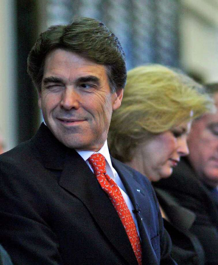 Gov. Rick Perry winks to a member of the Texas Senate before he delivers his State of the State message in the Texas House of Representatives, Feb. 6, 2007, in Austin. Texas first lady Anita Perry is in the background. Photo: Harry Cabluck, AP / AP