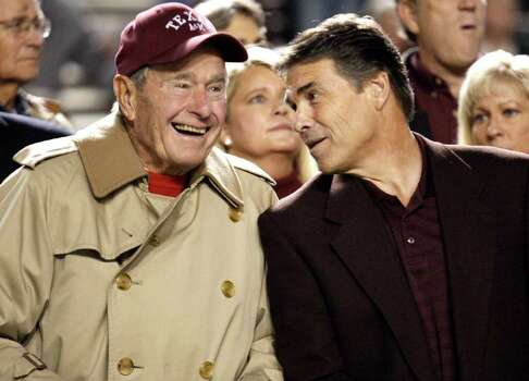 Texas Gov. Rick Perry talks with former President George H.W. Bush before an NCAA college football game between Texas and Texas A&M, Nov. 26, 2009, in College Station. Photo: AP