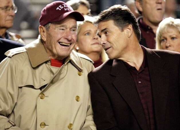 Texas Gov. Rick Perry, right, talks with former President George H.W. Bush before an NCAA college football game between Texas and Texas A&M on Thursday, Nov. 26, 2009, in College Station, Texas. Photo: AP
