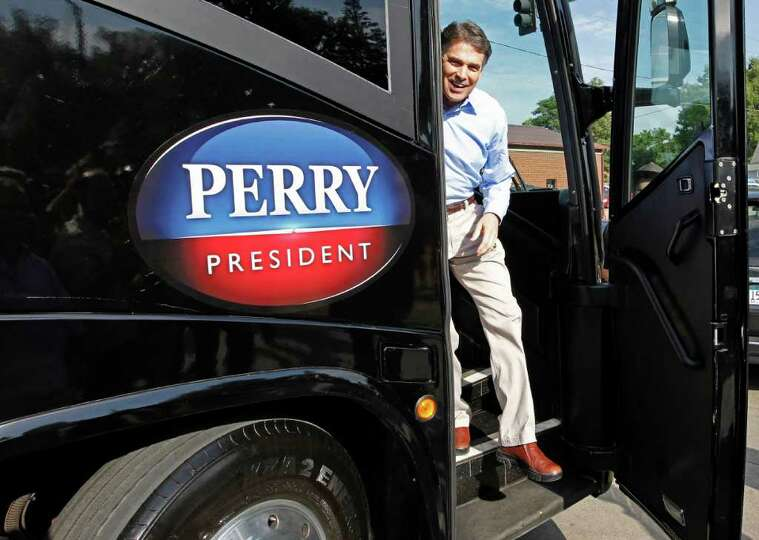 Republican presidential candidate, Texas Gov. Rick Perry, steps off his campaign bus as he visits th
