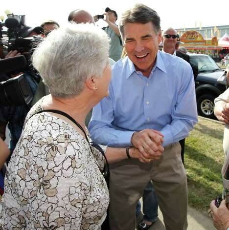 GOP hopeful Rick Perry, seen here at the Iowa State Fair, emphasizes employment gains in the private sector. Photo: AP