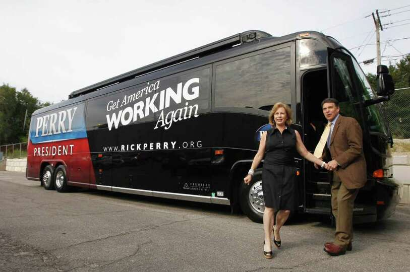 Republican presidential candidate, Texas Gov. Rick Perry and his wife Anita step off the campaign bu