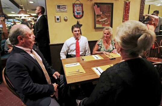 New Hampshire GOP chairman Jack Kimball (left) meets with Republican presidential candidate, Texas Gov. Rick Perry, and others, Aug. 18, 2011, during lunch at a cafe in downtown Dover, N.H. Photo: AP
