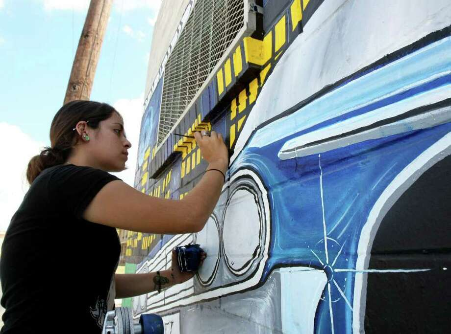 Andrea Rivas puts the finishing touches on a new mural on Guadalupe and El Paso Streets on Monday Aug. 22, 2011. Photo: HELEN L. MONTOYA, HELEN L. MONTOYA/hmontoya@conexionsa.com / hmontoya@express-news.net