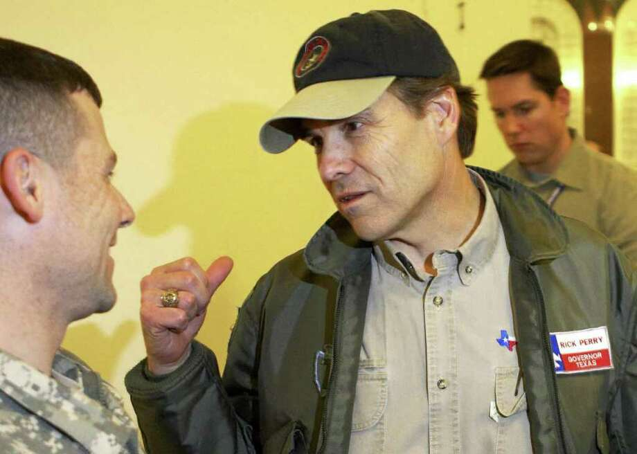 BAGHDAD, Iraq:  Texas Gov. Rick Perry speaks to a soldier during a trip to Baghdad 24 January 2006. Perry visited troops in a former Saddam Hussein palace, now used as a U.S. Embassy compound. AFP PHOTO/PHOTO/Jacob Silberberg-POOL Photo: POOL, AFP/Getty Images / 2006 AFP