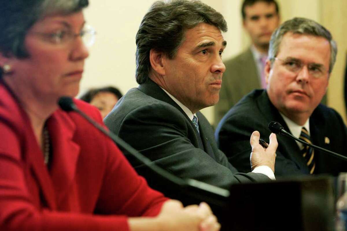 WASHINGTON - OCTOBER 19: Texas Governor Rick Perry (C) testifies as Florida Governor Jeb Bush (R) and Arizona Governor Janet Napolitano (L) listen during a hearing before the House Committee on Homeland Security on Capitol Hill October 19, 2005 in Washington, DC. The hearing was to examine the roles and responsibilities of local, state and federal agencies in disaster response.