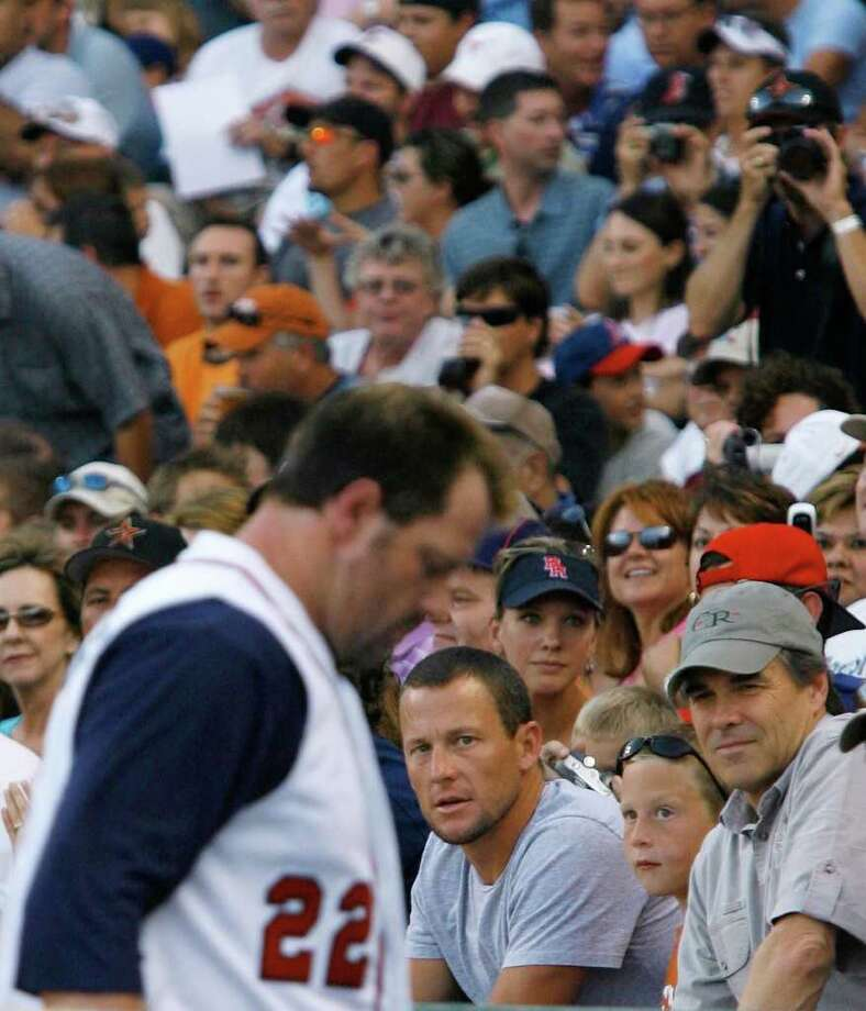 Roger Clemens, foreground, pitching for the Round Rock Express, returns to the dugout after striking out in a baseball game between the Express and the New Orleans Zephyrs on Friday, June 16, 2006, in Round Rock, Texas. Seated in the background, are retired pro cyclist Lance Armstrong, with his son, Luke, and Texas Gov. Rick Perry. Clemens is part-owner of the Express. Photo: HARRY CABLUCK, AP / AP
