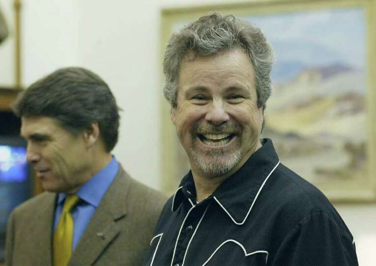 Singer and songwriter Robert Earl Keen, right, smiles during a meeting with Texas Gov. Rick Perry, i