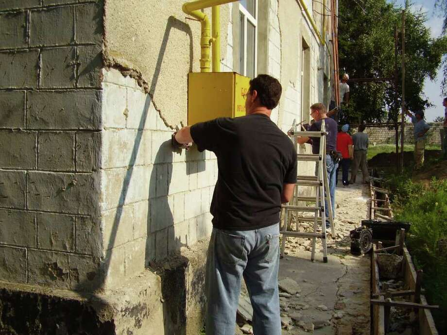 Pastor Scott Knight chips stucco from the outside of an old building in Ciniseuti, a village in a country of Moldova. Knight was one of nine men who represented the Pointe Fellowship in Tomball on a recent missions trip. Photo: Bryan Kirk