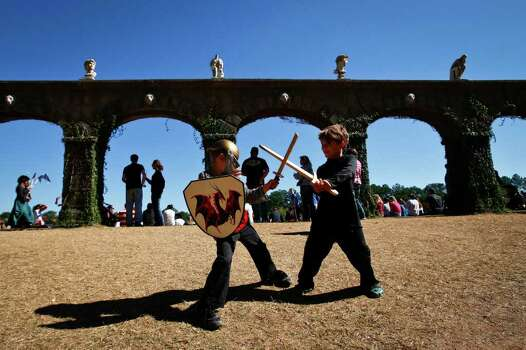 Eli Dawkins, 7, (left) and Linus Reeh, 6, battle with wooden swords before the start of the Jousting event at the Texas Renaissance Festival in Plantersville, Tx. Photo: Michael Paulsen, Staff / Houston Chronicle