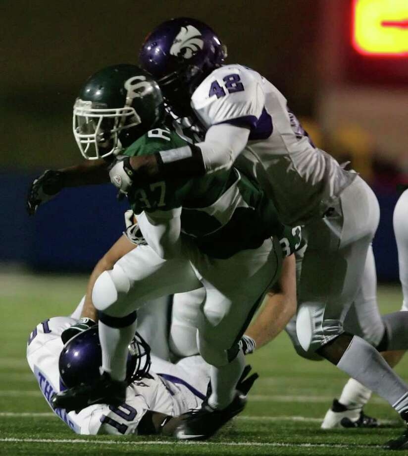 Stratford's Rodrick Taylor (37) is brought down by Humble's Devonta Smith (42) and Clifford Thomas during the second quarter of their playoff matchup, Friday at Tully Stadium. Photo: ERIC CHRISTIAN SMITH, Freelance / Freelance