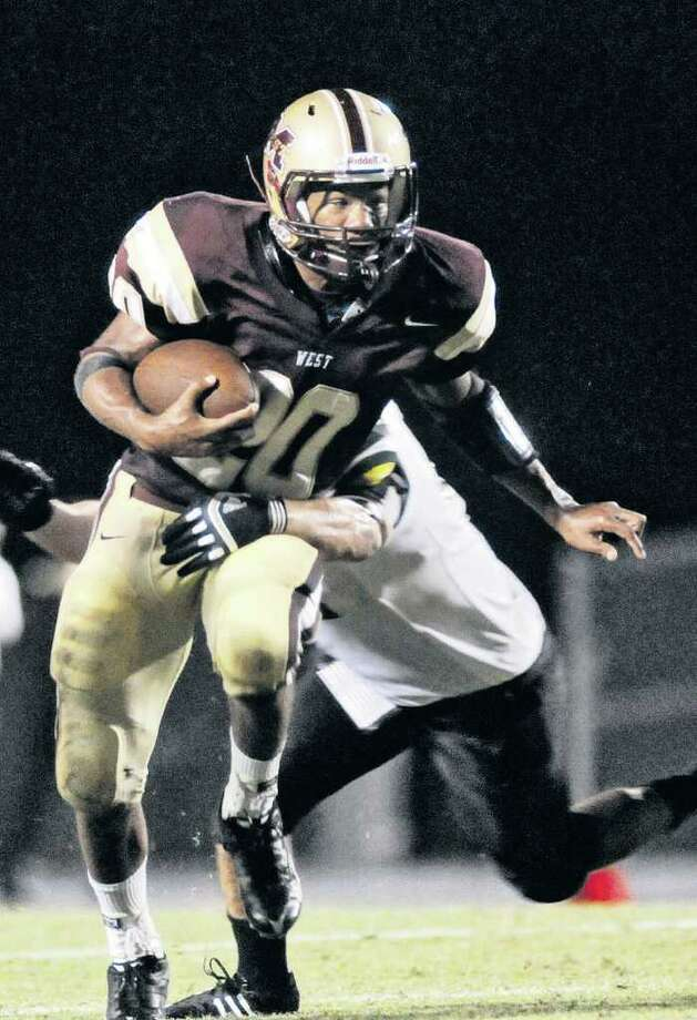 Magnolia West junior lrunning back Desmond Richards tries to escape the grasp of  a Kingwood Park defender. Photo by Jerry Baker Photo: Jerry Baker, Freelance / Freelance