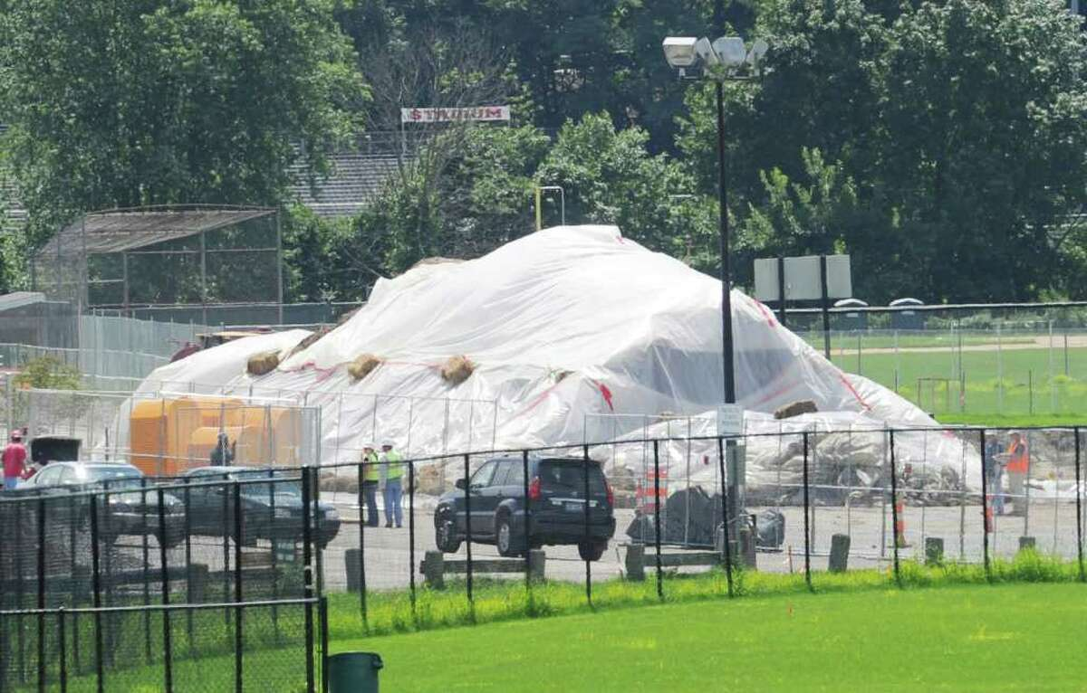 Tarps cover a pile of dirt in the western parking lot at Greenwich High School where construction and renovation work for the music instructional space and auditorium project is ongoing Wednesday afternoon, Aug. 24, 2011. Toxins unearthed during the project have closed all athletic fields adjacent to the lot.