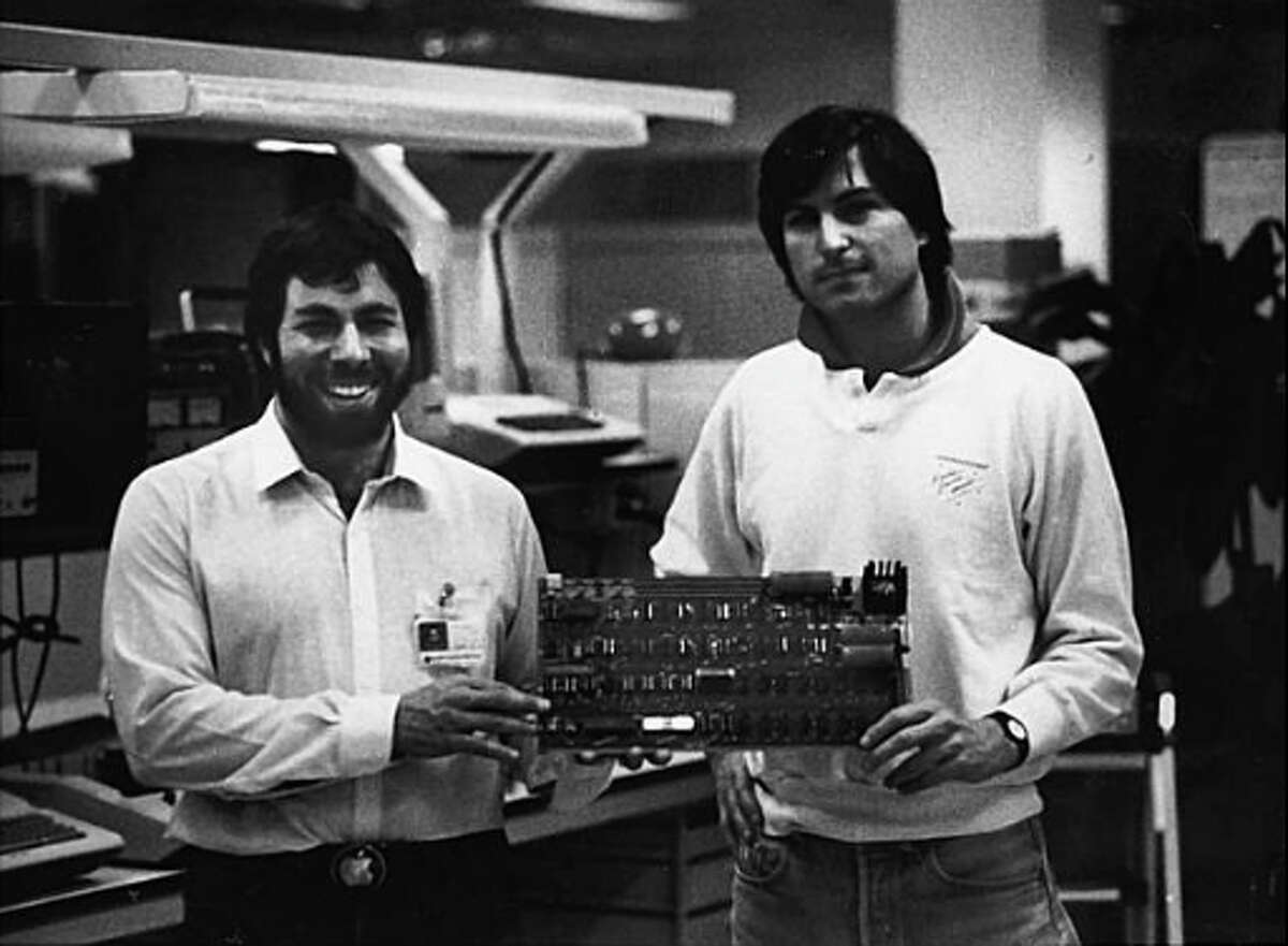 Steve Wozniak and Steve Jobs, co-founders of Apple Computer, with one of the original Apple I computer circuit boards.
