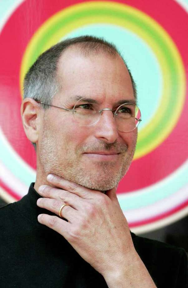 Steve Jobs, Apple Chief Executive Officer, poses during a photocall at EMI's offices in London, April 2, 2007. Apple annouced that EMI music company will make available for purchase its entire digital music back catalogue on the ITunes internet store in a business collaboration with Apple. Photo: CARL DE SOUZA, AFP/Getty Images / 2007 AFP