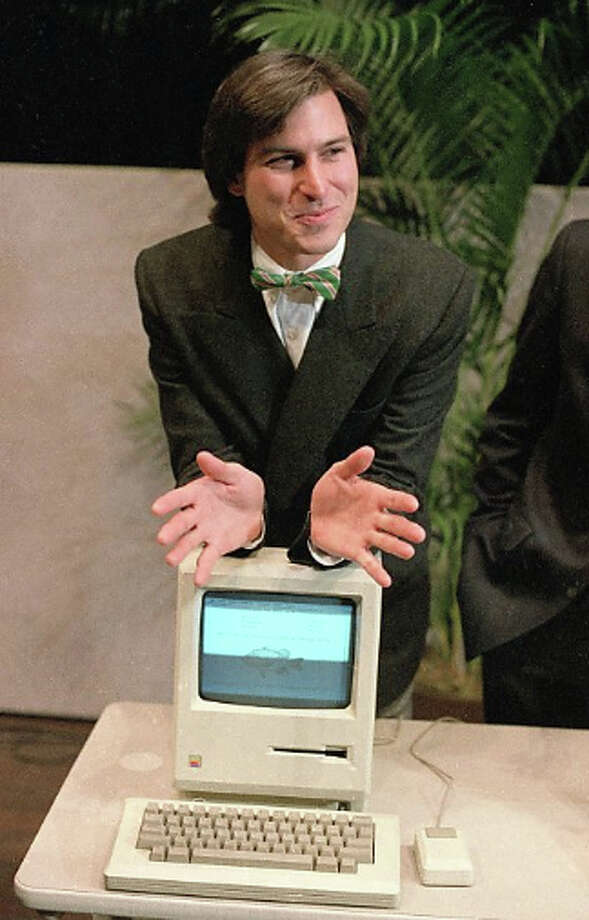 "Steve Jobs, chairman of the board of Apple Computer, leans on the new ""Macintosh"" personal comptuer following a shareholder's meeting in January 1984 in Cupertino. Photo: Paul Sakuma / AP"