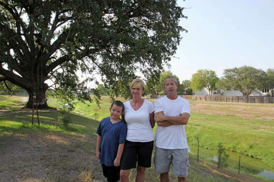 Harrison Shea, 8, stands with his parents Kay and Allen Shea, near a large oak tree behind their house in Nottingham Country subdivision. The tree sits on land where a proposed trail is planned. Photo: Suzanne Rehak, Freelance Photographer