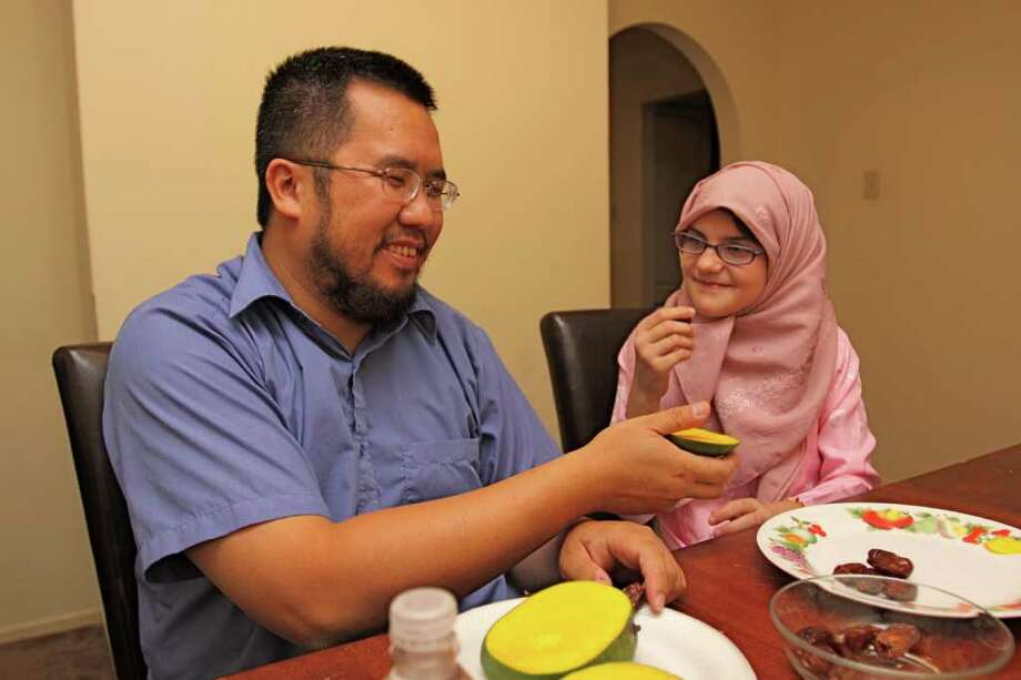 Hamza Bui and his step-daughter, Amy Williams, 10, broke the fast of not eating or drinking during daylight hours during Ramadan on August 18 by sharing mangoes, dates and water.  Suzanne Rehak/For the Chronicle Photo: Suzanne Rehak, Freelance Photographer