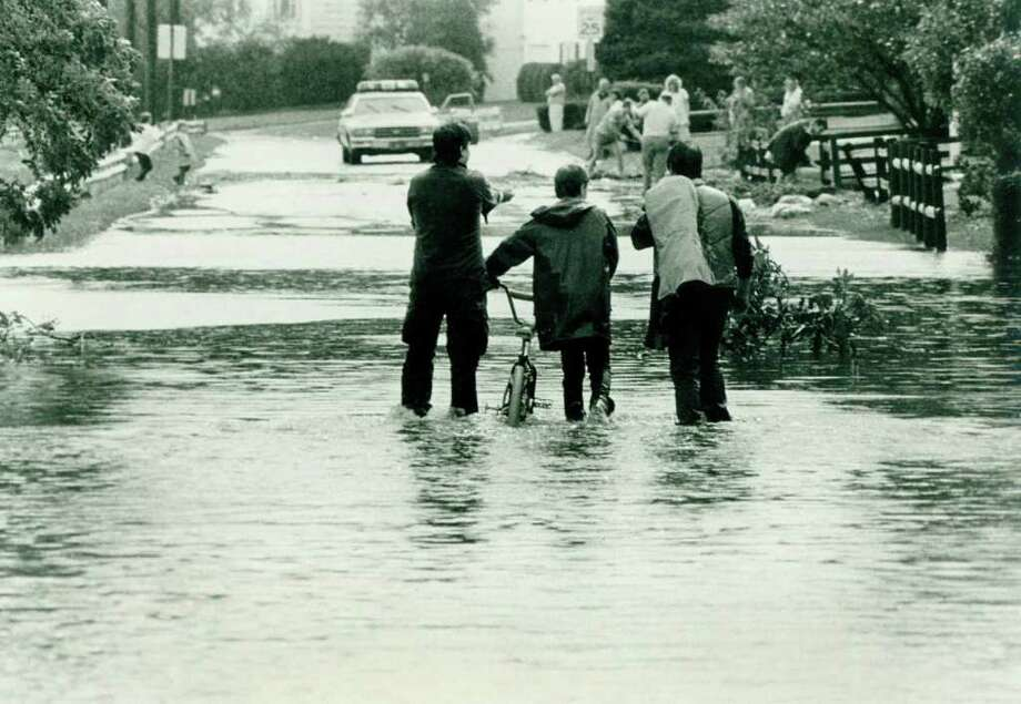Hurricane Gloria  Sept.  27, 1985 - Weed Ave along the Holly Pond which flooded. Kids who had a day off from school use the middle of the road for a walkway protected by police who warned cars away.  Tom Ryan Photo: File Photo, ST / Stamford Advocate File Photo