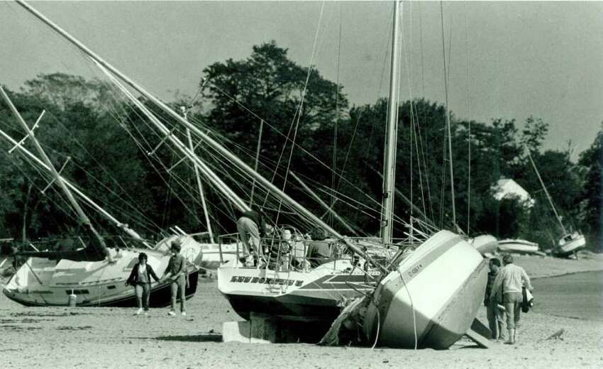 Hurricane Gloria Sept. 28, 1985 - sightseers and boat owners look over the sailboats beached on Calf Pasture Beach in Norwalk.