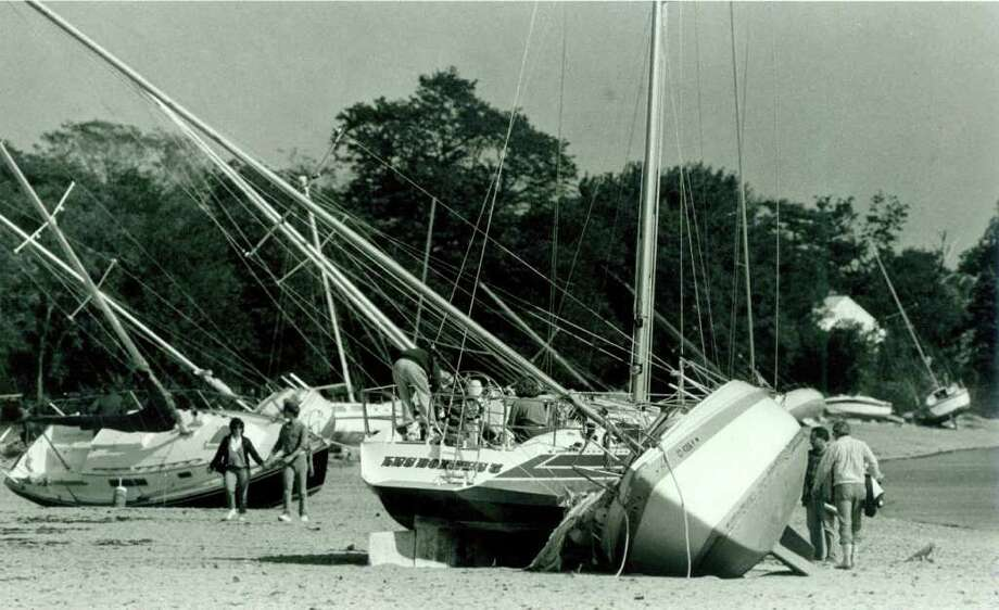 Hurricane Gloria  Sept.  28, 1985 - sightseers and boat owners look over the sailboats beached on Calf Pasture Beach in Norwalk. Photo: File Photo, ST / Stamford Advocate File Photo
