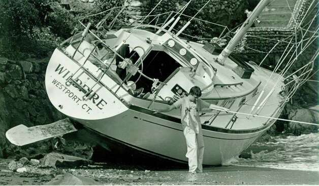 Hurricane Gloria  Sept.  27, 1985 - Adam Wansiewicz, with head down, and his brother Kieth, in rear of boat, watch over it for their parents who send for help. The boat washed ashore after it broke away from its mooring just off Bell Island.  The Wansiewicz are from Westport, CT. Wildfire     Glenn Osmundson Photo: File Photo, ST / Stamford Advocate File Photo