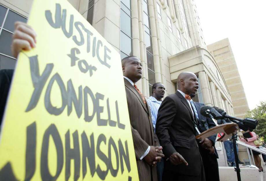 Gloria Rubac, left,  holds a sign with Quanell X, second from left, Yondell Johnson, center, and Deric Muhammad , right, during media conference outside the Harris County Criminal Justice Center, 1201 Franklin Street, Wednesday, Aug. 24, 2011, in Houston.   Yondell Johnson was assaulted by four white males while waiting for a Metro bus in downtown Houston on Saturday August 13th. Community activists held the conference asking that the Harris County District Attorney to declare this a hate crime. ( Melissa Phillip / Houston Chronicle ) Photo: Melissa Phillip, Staff / © 2011 Houston Chronicle